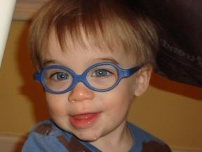 picture of a baby boy wearing glasses for farsightedness and pediatric cataracts