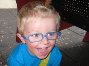 Cooper, 2 1/2 years old.  He wears glasses for farsightedness.  Frames are Miraflex.