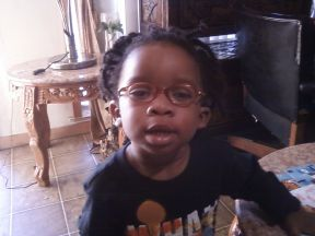Emani, 2 years old.  He wears glasses for farsightedness and aniridia.  Frames are Nickelodeon purchased at WalMart Optical.