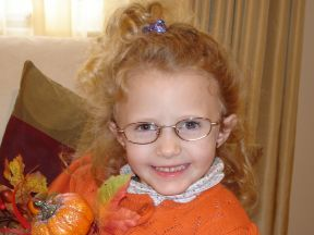 picture of a 4 year old girl in glasses.