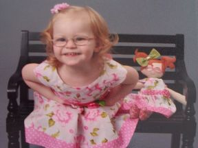 toddler girl in glasses for farsightedness with her doll who also wears glasses