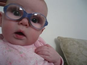 Penny, 3 months - she wears glasses for bilateral congenital cataracts.  She is wearing blue Disney Pooh frames. I've had to add pieces of fabric bandaid on the nose to help give some friction and keep them from sliding down her nose.