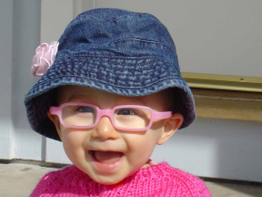 C - 14 months old; she started wearing glasses at around 7 months for farsightedness and strabismus. C's glasses are the rectangular shape frames by Miraflex.