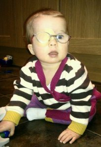 Evie in her patch and glasses at 8 months