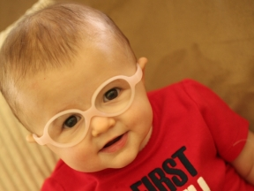 Lauren, 7 months old.  She wears glasses for farsightedness.  She is wearing Miraflex frames.