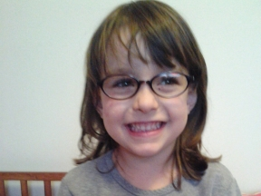 4 year old girl wearing glasses for astigmatism and thin optic nerve