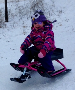 girl wearing an eye patch on a sled