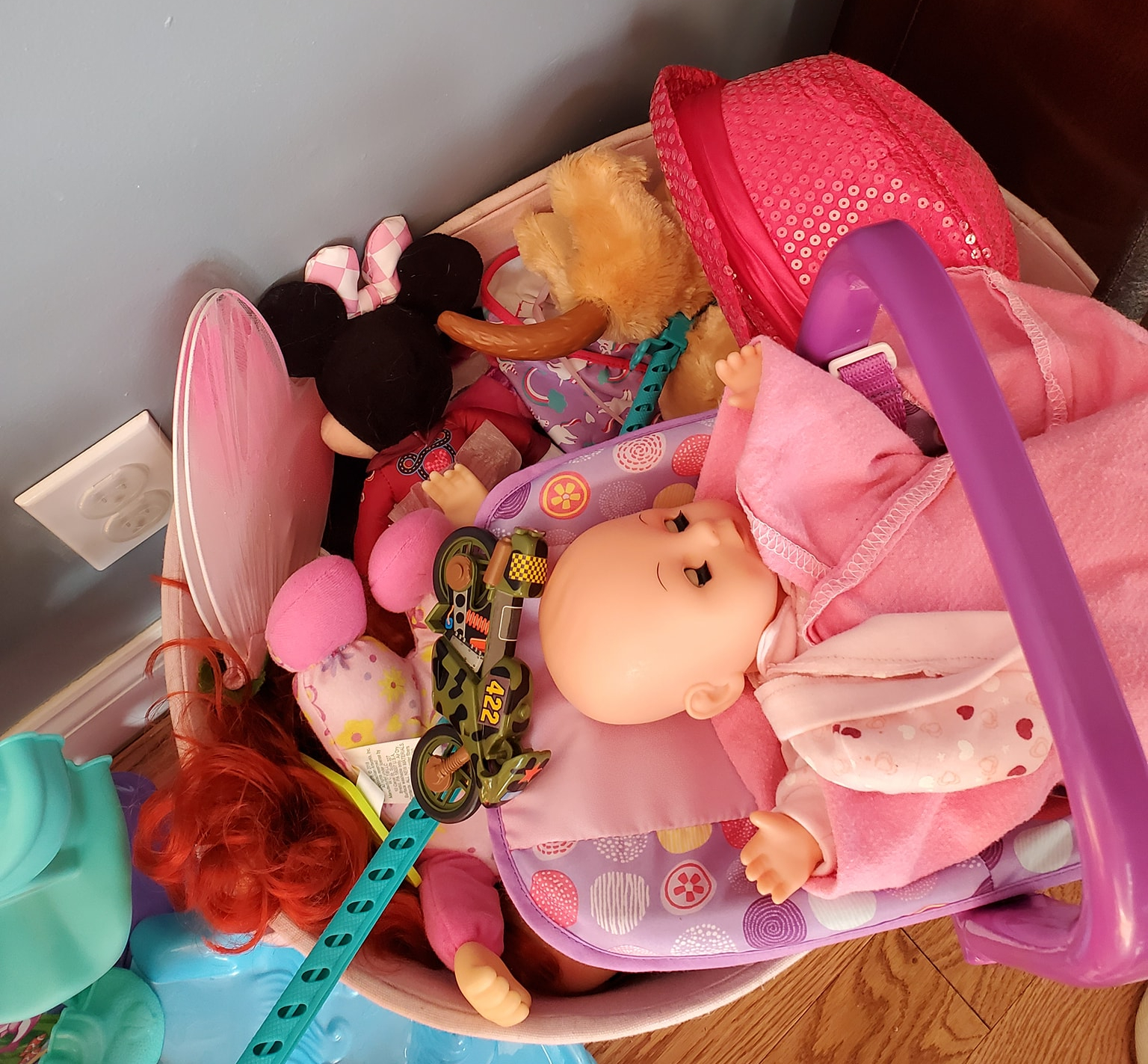 photo of a bin of a child's toys, including dolls, a hat, a motorcyle, dress up fairy wings, and a pair of children's glasses